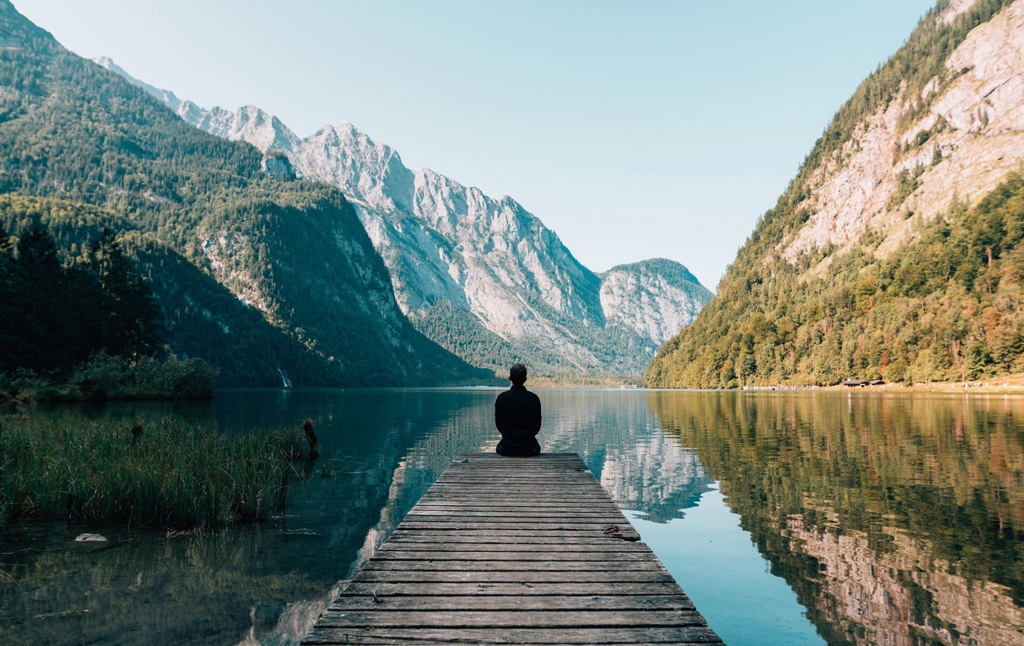 Sitting on a pier, overlooking lake, surrounded by mountains